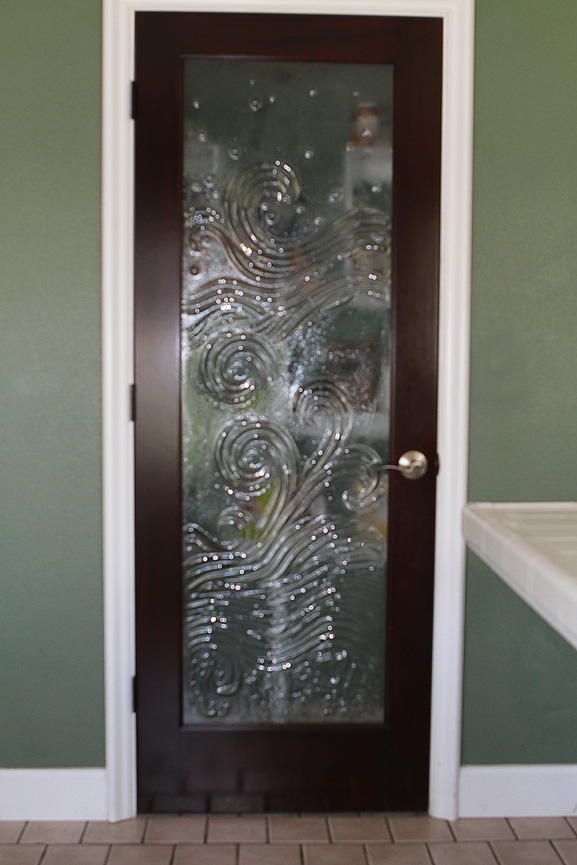 custom made wood door with scrolly glass insert