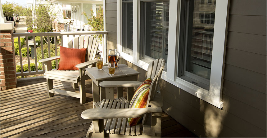 White Hardie Trim Windows-With-Light Brown Chairs On Porch